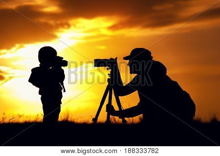 Silhouettes of young mother and little son having fun together outdoors. Woman and child photographing each other at setting sun light. Happy family relations.