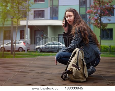 Girl speaks by mobile phone sitting on his haunches. The teenager in front of a building on a city street