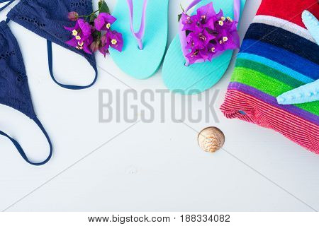 Summer beach fun - sandals with swimming suit, beach towel and starfish, copy space on white wooden background