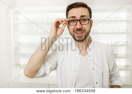 Man optometrist using glasses and positively looking at camera , standing at ophthalmic clinic. In the background a showcase with a many glasses