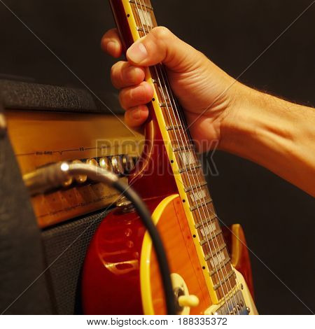 Hand puts guitar to combo amplifier on the black background. Shallow depth of field low key close up.