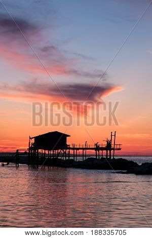 Stilt house in silhouette over the sea during a beautiful red sunset