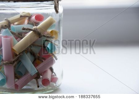 Glass jar with colored notes with blur and toning