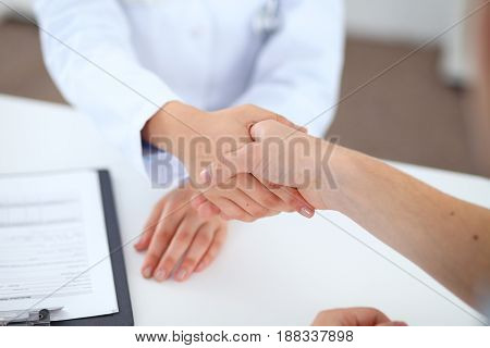 Partnership, trust and medical ethics concept. Doctor and patient shaking hands