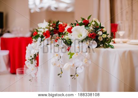 Newlyweds table decorated with gorgeous bouquet of orchid and roses, in white and red colours