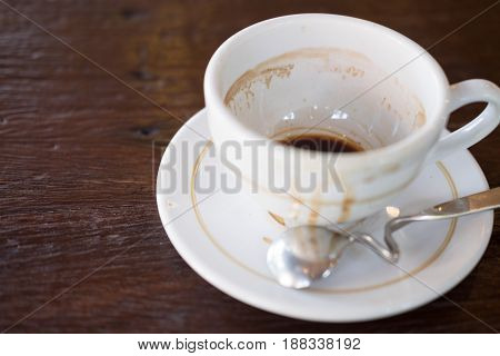 Coffee cup white color empty and dirty after drinking on wooden table