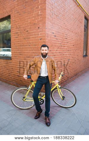 Young Stylish Man With A Beard Sitting On A Brick Background Bicycle