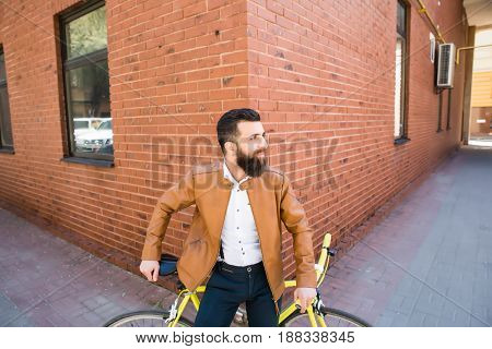 Young Handsome Man With A Beard Against Of A Brick Wall Sits On A Bicycle