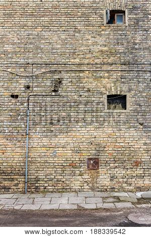Old yellow brick wall with small windows and sidewalk architecture detail background