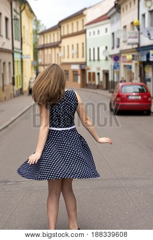 Light brunette is dancing on the street