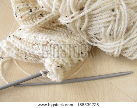 Hand knitted in cream white and knitting needles