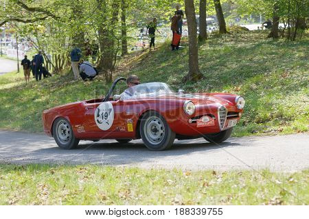 STOCKHOLM SWEDEN - MAY 22 2017: Red Alfa Romeo classic car from 1957 driving on a country road in the public race Gardesloppet in the forests at Djurgarden Stockholm Sweden. May 22 2017