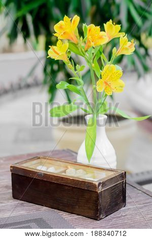 Old Style Sugar Capacity With Yellow Flower In Vase On The Wooden Table