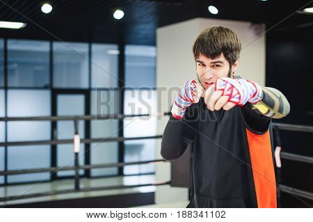 Professional Muay Thai Fighter. Male Boxer In Training Sportswear, An Exercise In Sports Hall, Fight