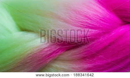 texture of green and pink colored kanekalon material for Afro-braids and other hairstyles close-up shallow depth of field