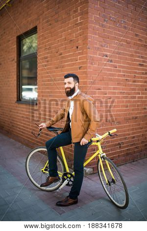 Young Stylish Man With A Beard Sitting On Bicycle On A Brick Background