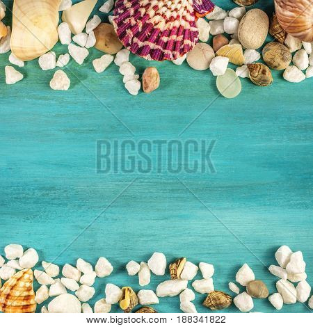 A square overhead photo of sea shells and pebbles, forming a frame on a vibrant turquoise background texture with plenty of copy space