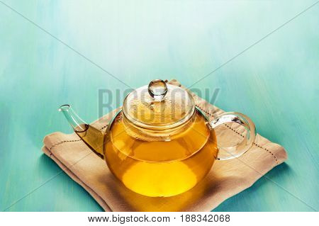 A photo of a teapot full of tea, shot on a teal blue texture with a place for text