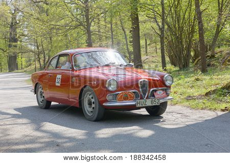 STOCKHOLM SWEDEN - MAY 22 2017: Red Alfa Romeo Guiletta classic car from 1960 driving on a country road in the public race Gardesloppet in the forests at Djurgarden Stockholm Sweden. May 22 2017