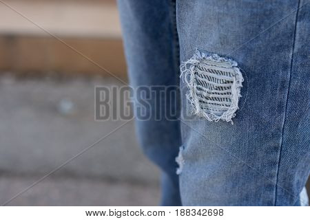 Detail of boy's jeans with a hole