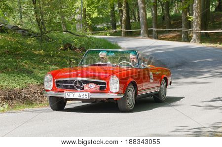 STOCKHOLM, SWEDEN - MAY 22, 2017: Red Mercedes BENZ 230 SL classic car from 1965 driving on a country road in the public race Gardesloppet in the forests at Djurgarden, Stockholm, Sweden. May 22, 2017
