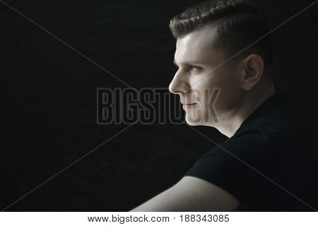 Side view head and shoulders young man portrait in low-key studio lighting
