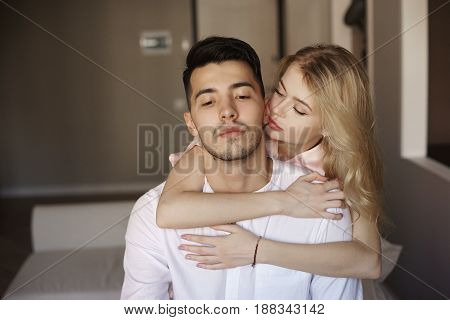 Young romantic couple at home. Caucasian blonde woman and brunette man. Lovers hugging in living room.