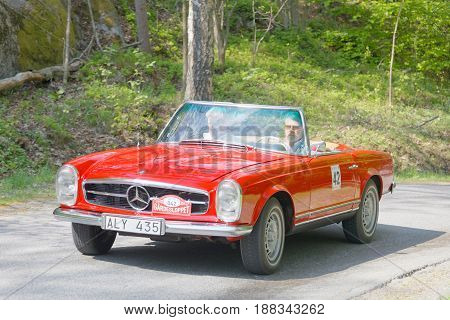 STOCKHOLM SWEDEN - MAY 22 2017: Red Mercedes BENZ 230 SL classic car from 1965 driving on a country road in the public race Gardesloppet in the forests at Djurgarden Stockholm Sweden. May 22 2017