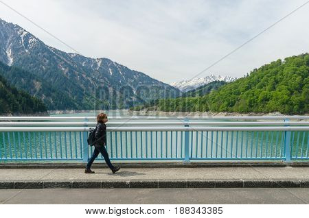 Female traveler and kurobe dam at tateyama kurobe alpine route in japan