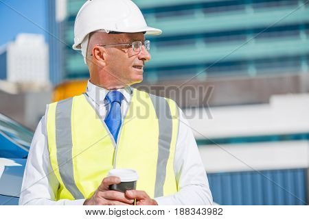 Senior engineer man in suit and helmet outdoor having coffee