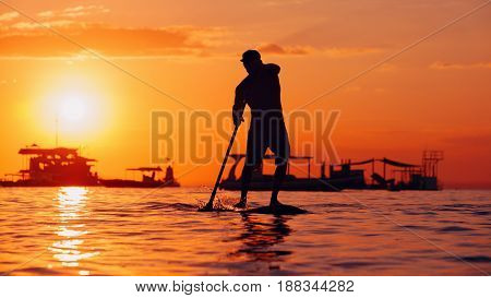 Active paddle boarder. Black sunset silhouette of young sportsman paddling on stand up paddleboard. Healthy lifestyle. Water sport SUP surfing tour in adventure camp on family summer beach vacation.