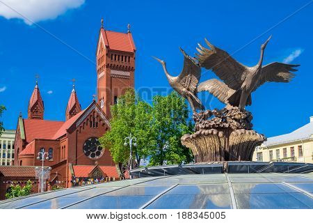 Minsk, Belarus - May 24, 2017: Church Of Saints Simon And Helena (red Church) And Sculpture Of Bronz