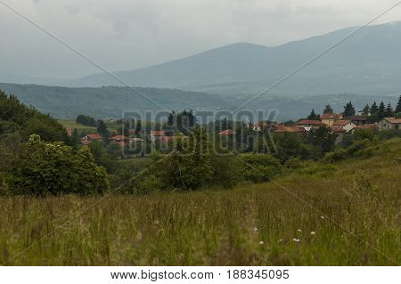 Scene with mountain glade, forest and residential district of bulgarian village Plana mountain, Bulgaria