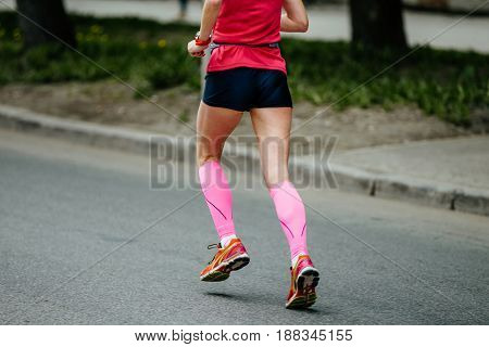 back runner girl in pink compression socks running street of city