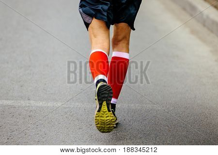 back feet men runner in red compression socks running street