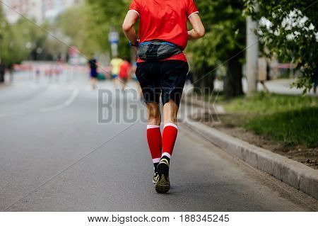 back man runner in red compression socks running street of the city