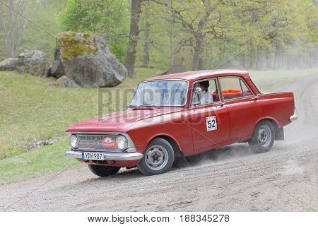 STOCKHOLM SWEDEN - MAY 22 2017: Red Moskovitch classic car from 1968 driving on a country road in the public race Gardesloppet in the forests at Djurgarden Stockholm Sweden. May 22 2017