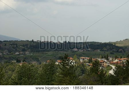 Scene with mountain glade, forest and residential district of bulgarian village Plana, Plana mountain, Bulgaria