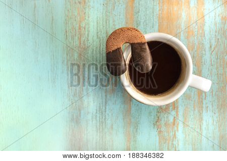 A photo of a cookie in the form of a horseshoe on top of a white cup with black coffee, shot from above on a wooden board texture