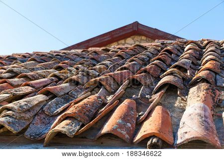Old red tile roof top with blue sky on background