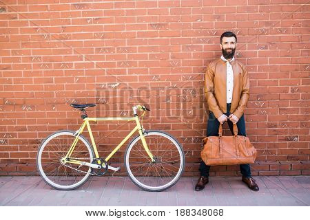 Young Stylish Man With Beard In A Brick Background Standing Near The Bike With Bag In Hands