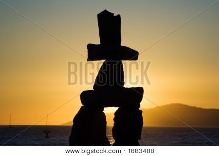 An Inukshuk Over A Sunset - Silhouette
