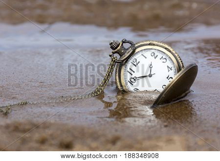 round pocket watch with hands lying on the wet sand water time