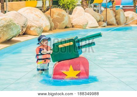 Young Child Having Fun With Water Cannon In Aqua Park