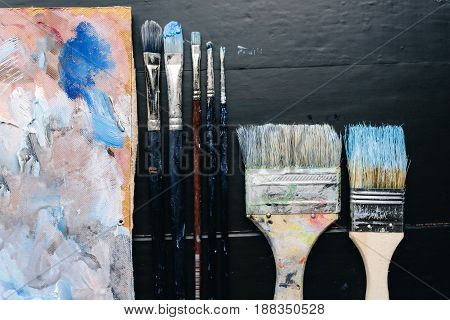 Artistic brushes and a palette lie on a black wooden table. Artist Tools