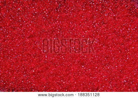 Crimson-red glass beads background - closeup beads texture. Abstract red background