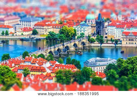 Scenic summer aerial panorama of the Old Town pier architecture with Charles Bridge and Vltava river in Prague, Czech Republic with tilt shift miniature effect