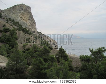 Summer overcast seascape. Stones and rocks by the sea against mountains and gray sky with clouds. Travel and nature background. Vacations in Crimea