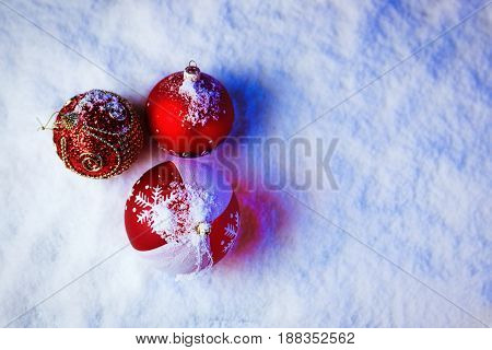 Ornate christmas balls in snow with blue backlight