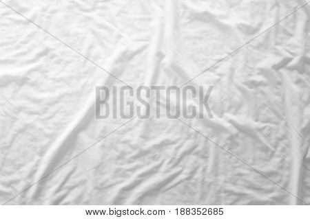Top view of unmade bedding sheets or white fabric wrinkle texture background